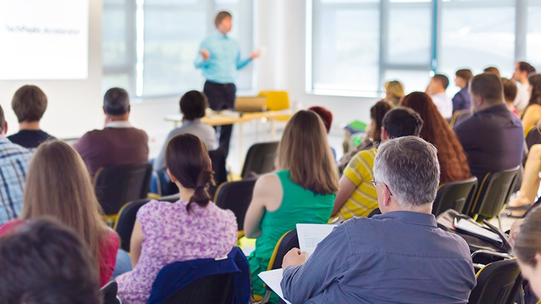 A group of teachers listening to a speaker at a professional development event